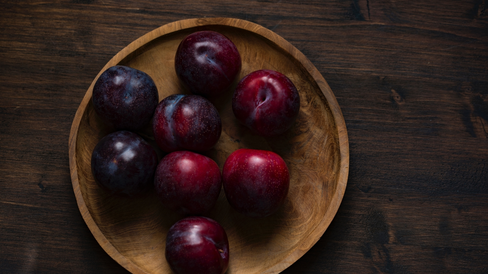 Image is of a wooden bowl containing 8 ripe plums