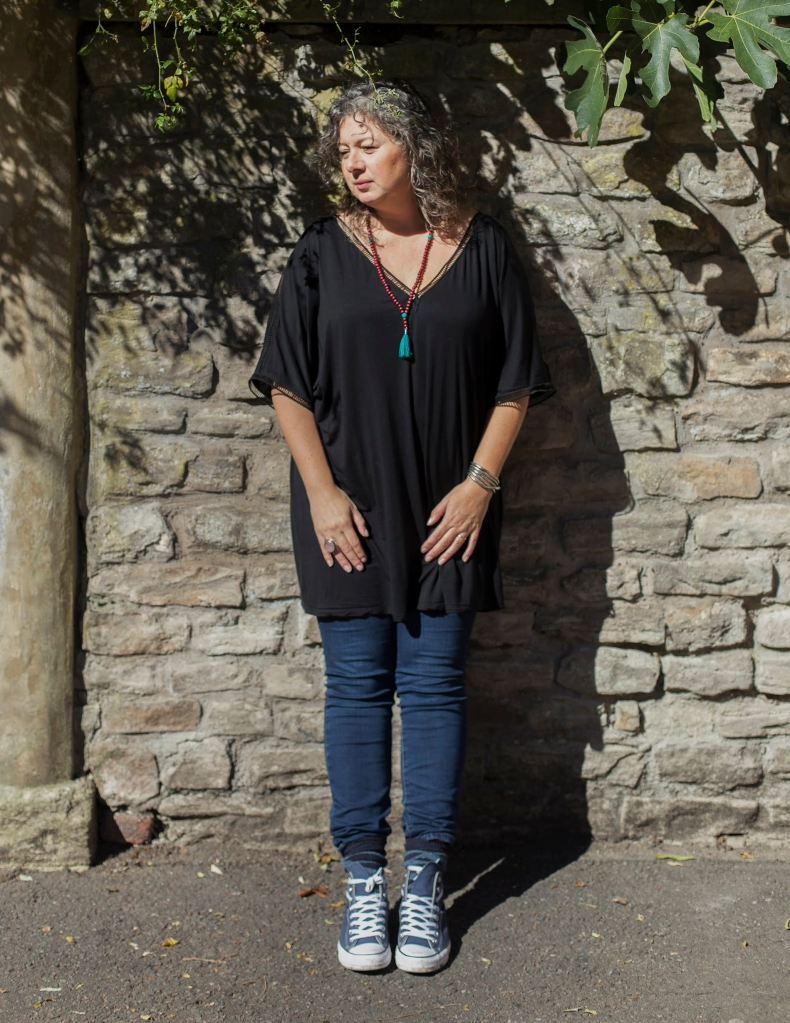 Image is a full length portrait of Florence Neville, a white woman with wavy grey hair in a loose black top, blue jeans and blue converse. She is standing by a stone wall with the branches of a fig tree overhead.