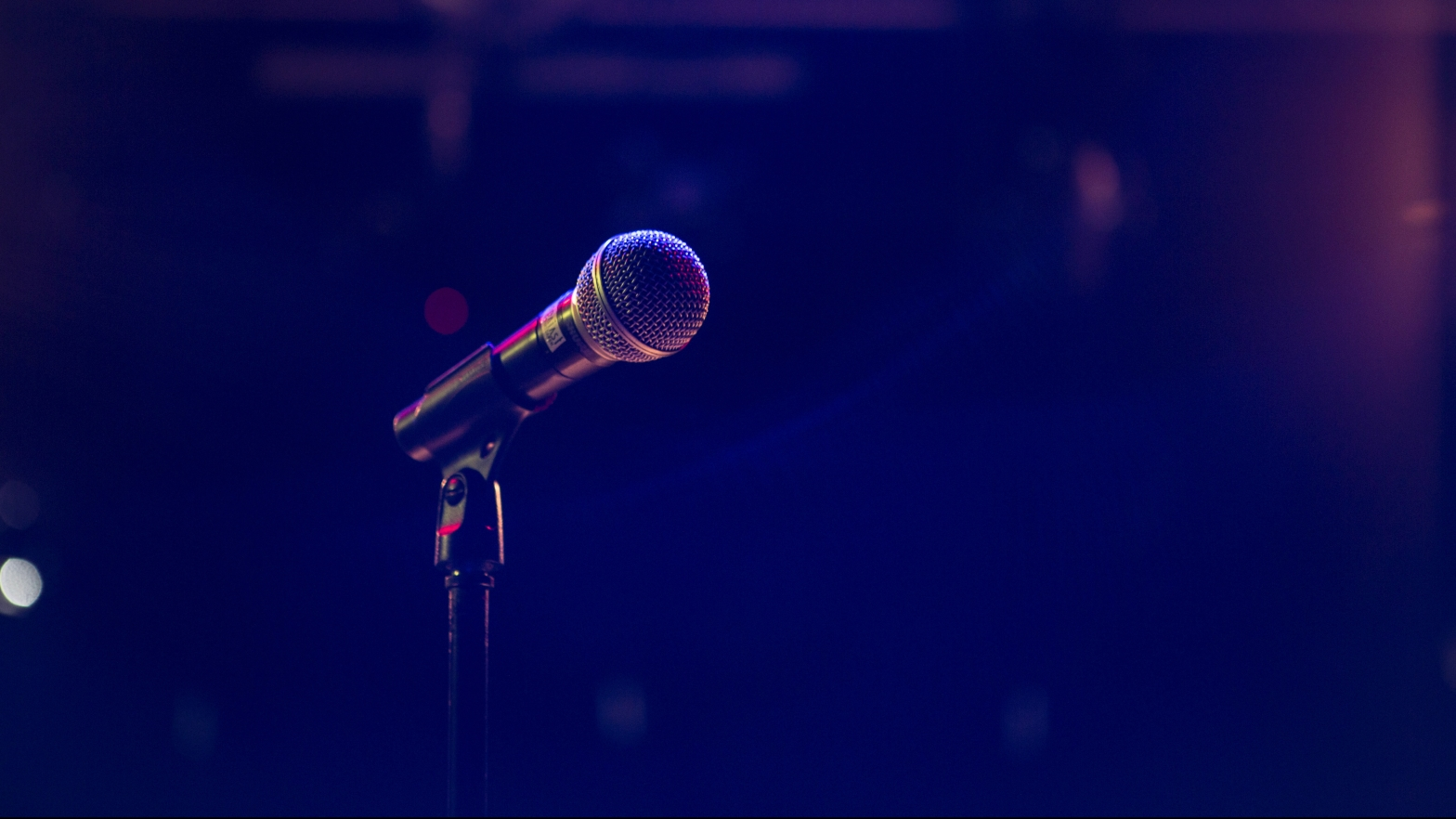 A microphone, probably on a stage, with hazy lighting