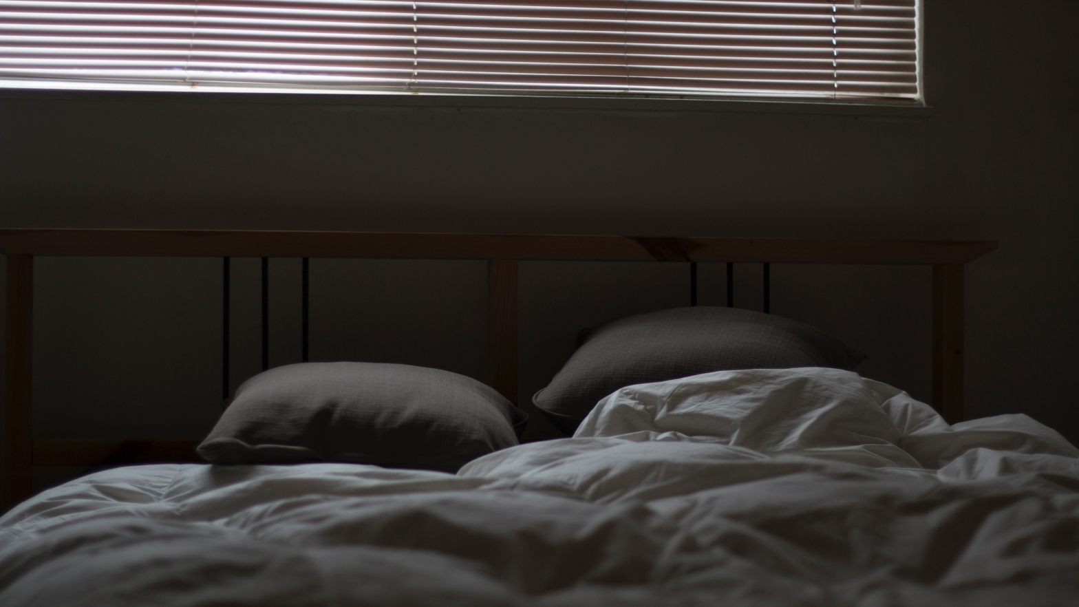 Image is of an unmade bed under a window with slatted blinds