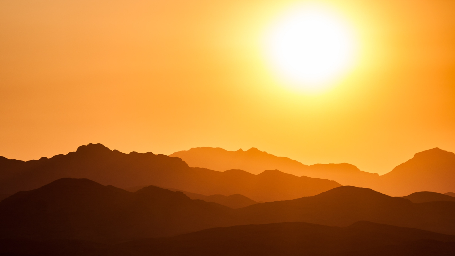 Image is of a sunrise over mountains