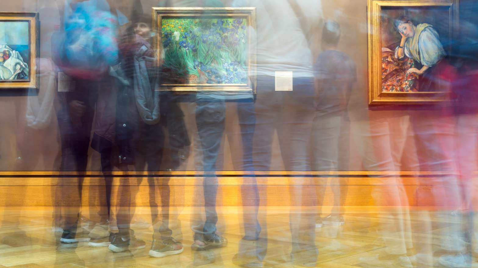 Image shows a group of people standing in front of paintings in an art gallery. The photo has been taken with slow shutter speed so that the people are blurred and the paintings are in focus.