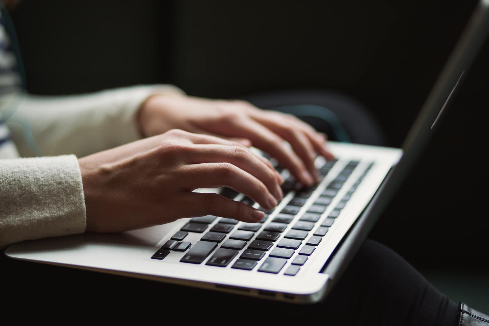 Image shows hands typing on a laptop keyboard