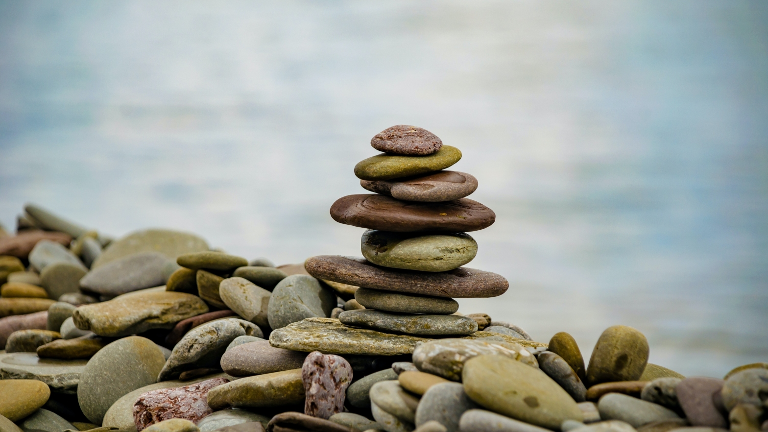 Photo of flat pebbles balanced in a pile on the beach