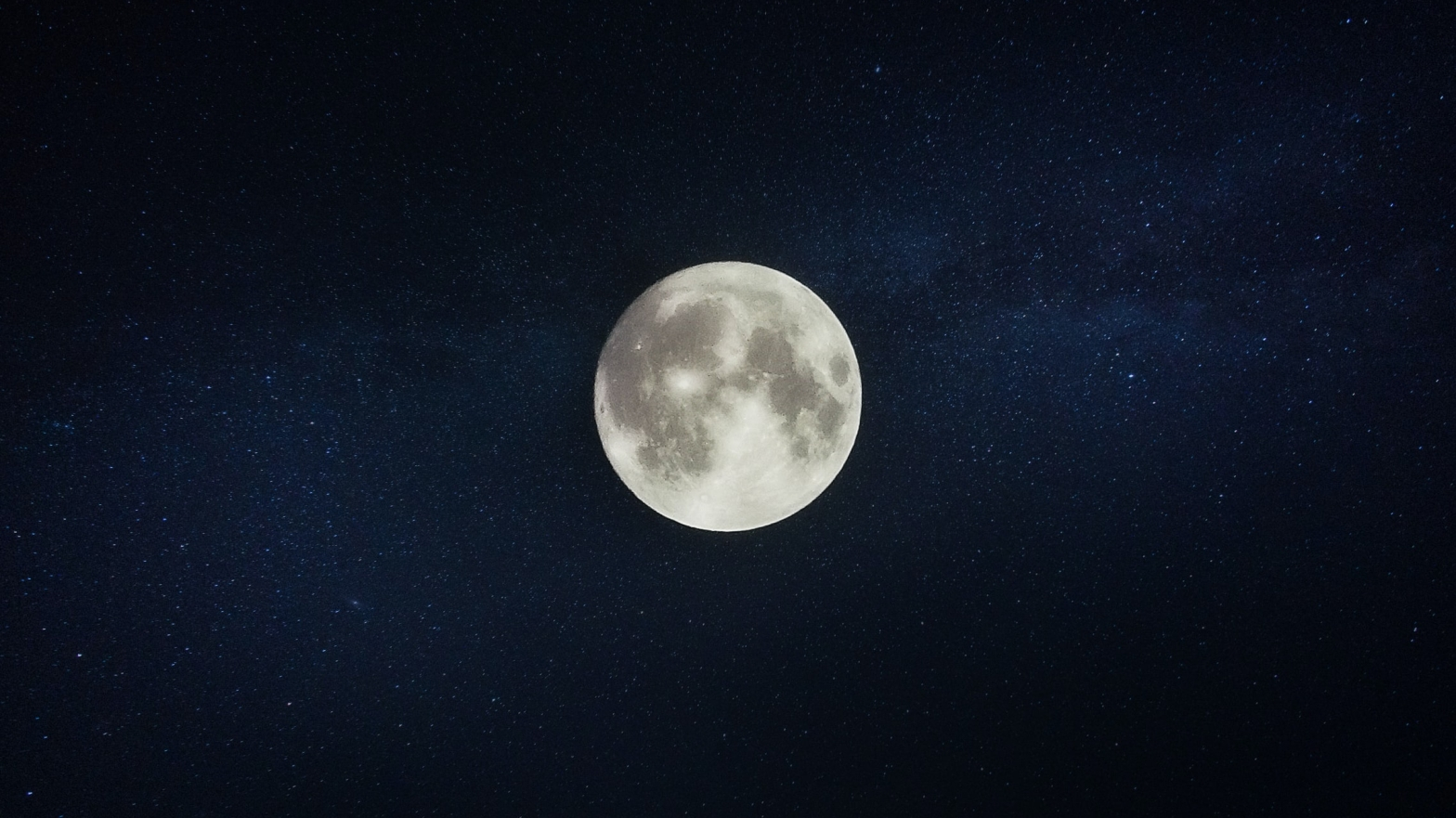 Image is a photo of a full moon in a dark starry sky