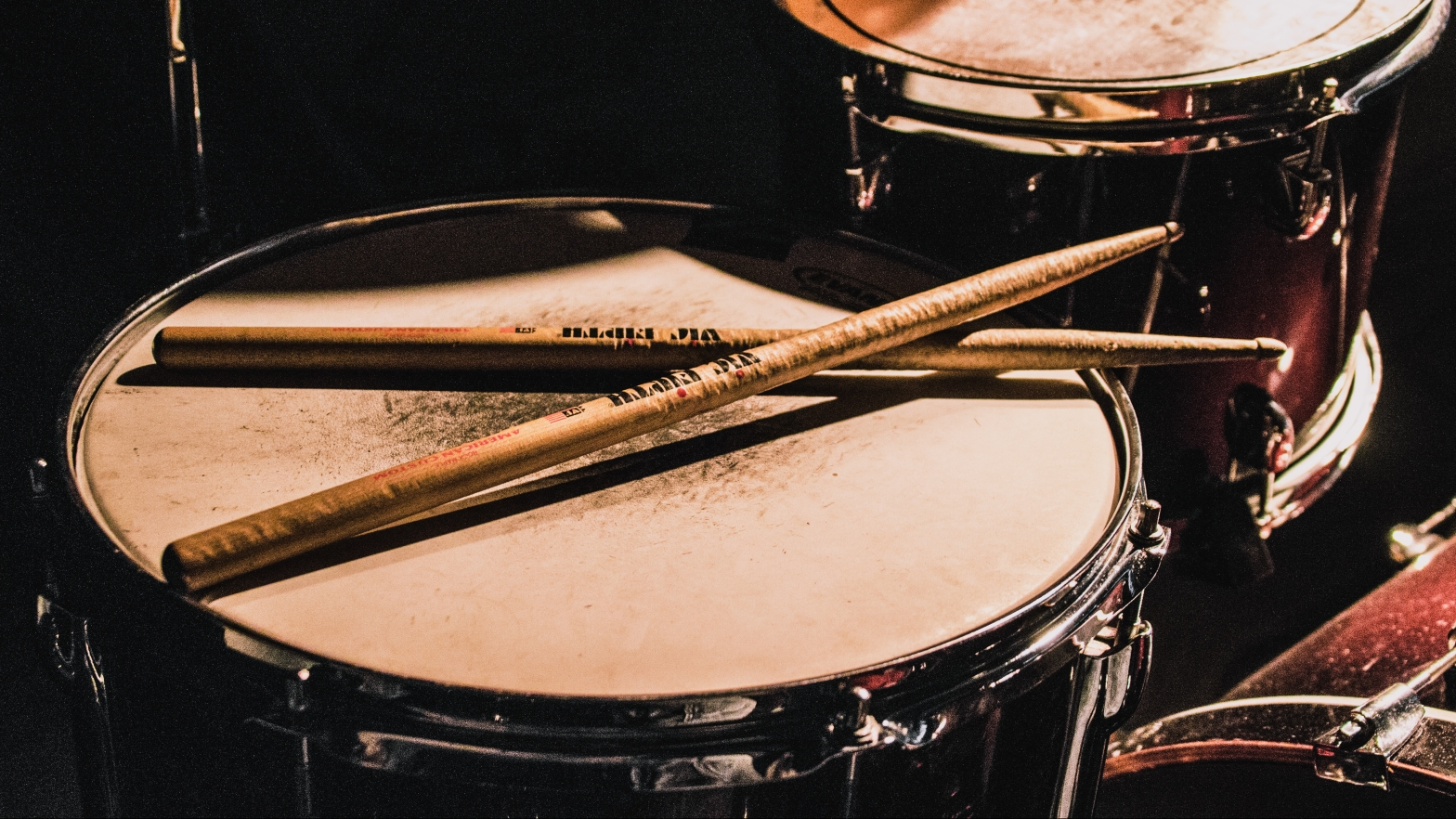 Image is a photo of a set of well used drums with somewhat battered looking sticks laid on the snare