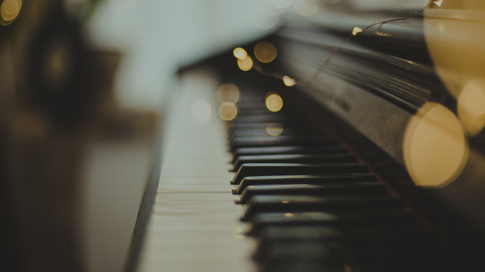 photo of piano keys strewn with out of focus fairy lights